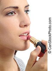 Close up of a beautiful woman applying a lipstick on lips