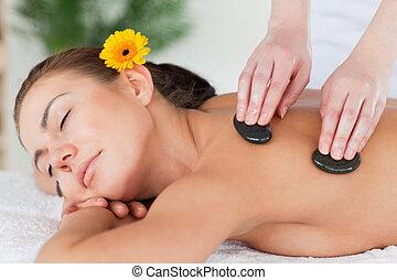 Close up of a beautiful woman enjoying a hot stone massage
