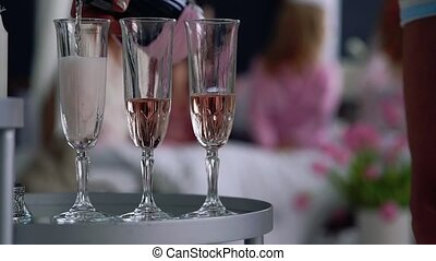 Close-up of a beautiful woman fills with champagne glasses...