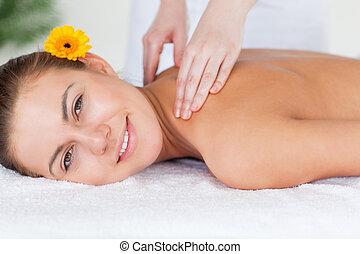 Close up of a beautiful woman having a shoulder massage