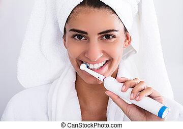 Beautiful Woman In Bathrobe Brushing Teeth