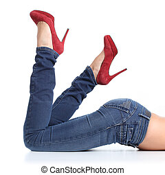 Close up of a beautiful woman legs with blue jeans and red heels isolated on a white background