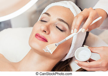 Close-up of a beautiful woman relaxing during facial treatment i
