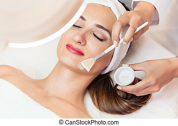 Close-up of a beautiful woman relaxing during facial treatment in beauty center