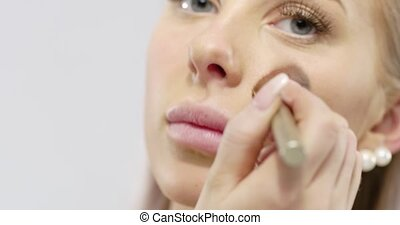 Close-up of a beautiful young woman applying dry cosmetic...