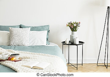 Close-up of a bed with pale sage green and white linen, pillows and a blanket in a sunny bedroom interior. A round black metal side table with vases and flowers beside the bed. Real photo