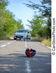 Close-up of a bicycling helmet fallen on the asphalt next to a bicycle after car accident on the street