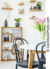 Close-up of a black chair and white table with tulips, and...