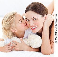 Close-up of a blond little girl kissing her mother lying on a bed