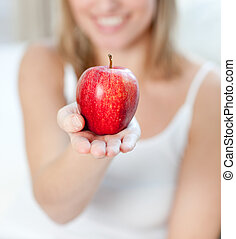 Close-up of a blond woman showing an apple