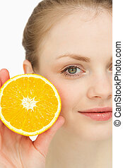 Close up of a blonde-haired girl presenting an orange...