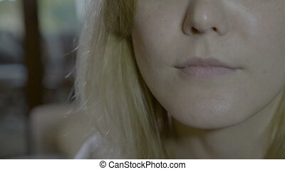 Close up of a blonde woman mouth swallowing an aspirin pill...