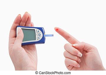 Close up of a blood glucose meter utilization