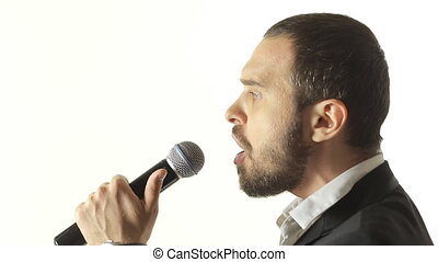 Close-up of a blue-eyed man with a beard wearing a jacket singing a song into the microphone in a studio