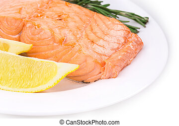 Close-up of a boiled salmon on white plate.