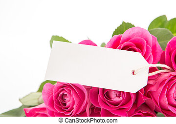 Close up of a bouquet of pink roses with a blank day card on a white background