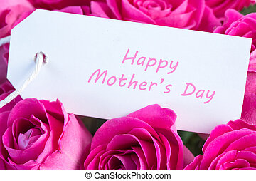 Close-up of a bouquet of pink roses with happy mothers day written in pink on a card