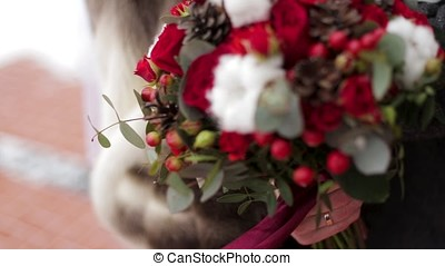 Close up of a bride holding a wedding bouquet with red roses. Bride holding flowers