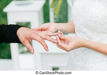 Close-up of a bride putting  wedding ring on  groom