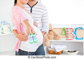 Close-up of a bright pregnant woman holding baby shoes while...