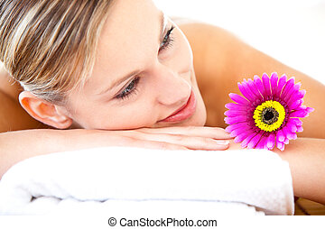 Close-up of a bright woman lying on a massage table with a flower in a health spa
