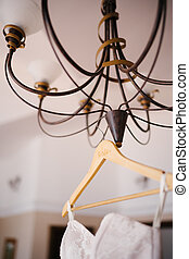 Close-up of a brown chandelier with a wooden hanger and a wedding dress on it.