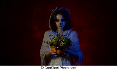 Close up of a bunch of flowers in hands os a girl staring at the camera. Young beautiful woman with art make-up is participating in Halloween party.