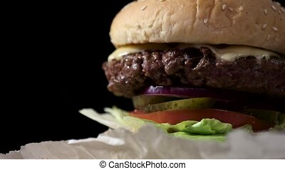 Close-up of a burger. Fresh lettuce and grilled meat. Melted...
