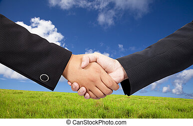 Close-up of a business people shaking hands against blue sky and green background