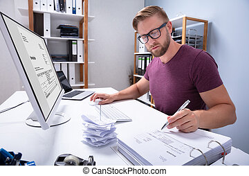 Businessman Checking Invoice On Computer