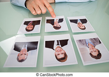 Businessman Hand Choosing Photograph Of A Candidate