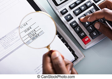 Businessman Holding Magnifying Glass Over Invoice
