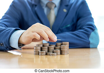 Close-up Of A Businessman Making Stack Of Coins