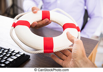 Businessman's Hand Passing A Lifebuoy To His Partner