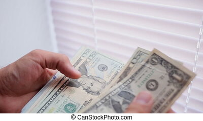 Close-up of a businessman's hands counting hundred dollar bills at a table