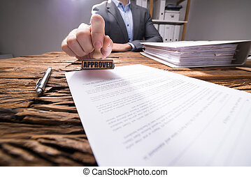 Close-up Of A Businessperson Approving Document