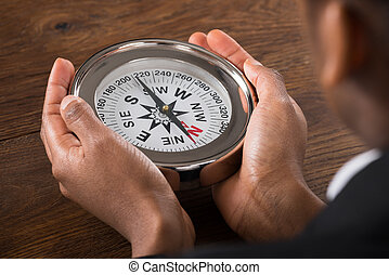 Businessperson Hand Holding Compass - Close-up Of A...
