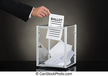 Businessperson Hand Putting Ballot In Glass Box - Close-up...
