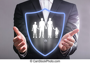 Businessperson's Hand With Shield Protecting Family