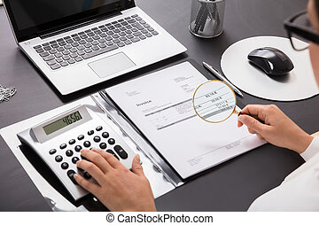 Businesswoman Looking Invoice Through Magnifying Glass