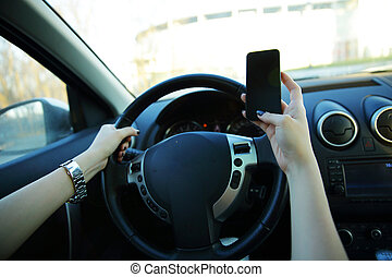 Close-up of a businesswoman sending a text while driving to...