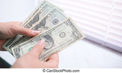 Close-up of a businesswoman's hands counting hundred dollar bills at a table
