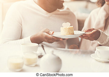 Close up of a cake being held by a nice couple
