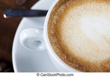 Close-up of a cappuccino coffee cup with milk foam -...
