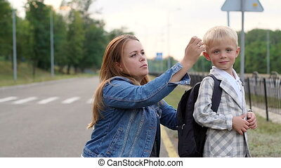Close-up of a caring mother adjusts the backpack on his back before school.