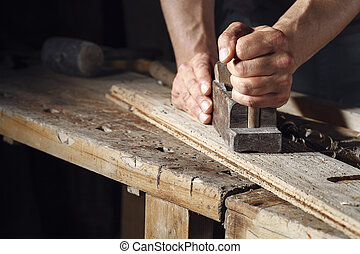 carpenter planing a plank of wood with a hand plane - Close...