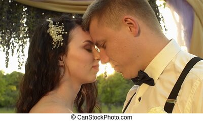 Close-up of a charming couple. Caucasian newlyweds closes their eyes with pleasure. Loving couple hugging each other at sunset.