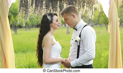 Close-up of a charming couple, man speaking the words of love to his lovely sweetheart. Dark-haired woman and a man with short hair in wedding dresses.