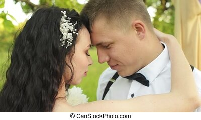 Close-up of a charming young couple. Caucasian newlyweds closes their eyes with pleasure. Girl with a comb in her hair hugs her boyfriendLoving couple hugging each other at sunset.