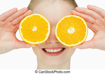 Close up of a cheerful woman placing oranges on her eyes...